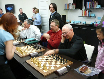 Rex Sinquefield, playing the Sicilian in a simul game against Jennifer Shahade. World Youth representative Margaret Hua looks on.